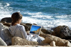 Young woman using a laptop by the sea. Young woman on the rocks near the sea using a white laptop Royalty Free Stock Image