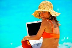 Young woman using laptop by the sea. Young woman using laptop on the beach Royalty Free Stock Photo
