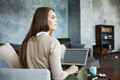 Young Woman Using Laptop while Sitting on Comfortable Sofa Stock Photos