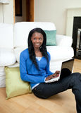 Young woman using a laptop sitting on the floor Royalty Free Stock Image