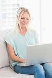Young woman using laptop while sitting on sofa Stock Photo