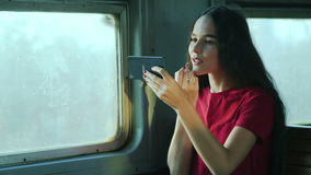 Young woman using laptop sitting in train stock video footage