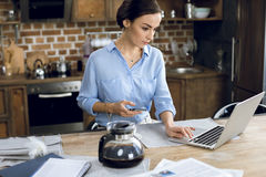 Young woman using laptop and smartphone at morning Royalty Free Stock Photos