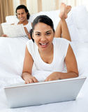 Young woman using a laptop smiling at the camera Royalty Free Stock Photos
