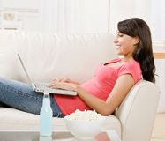 Young woman using laptop on sofa at home Stock Photography