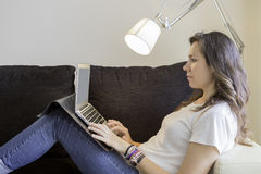Young woman using a laptop on a sofa Stock Photos