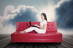 Young woman using laptop on sofa Stock Images