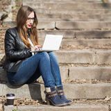 Young woman using laptop on stairs in the park Royalty Free Stock Photo