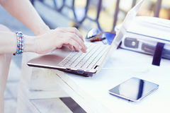 Young woman using laptop and typing outdoor. Unrecognizable young woman working on laptop and typing on the keyboard outdoors Stock Photography