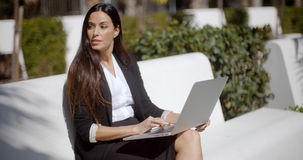 Young woman using a laptop on a white park bench Royalty Free Stock Photo