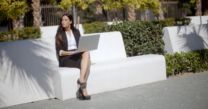 Young woman using a laptop on a white park bench Royalty Free Stock Photography