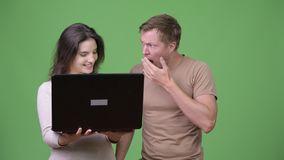 Young woman using laptop with young man looking shocked. Studio shot of young handsome Scandinavian man and young beautiful woman together against chroma key stock footage
