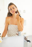 Young woman using makeup brush in bathroom Stock Images