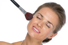 Young woman using makeup brush Royalty Free Stock Images