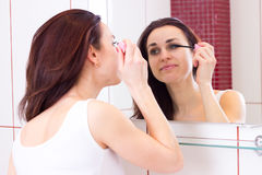 Young woman using mascara in bathroom Royalty Free Stock Photography