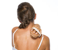 Young woman using massager . rear view Stock Image