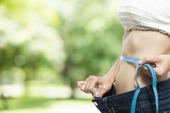 Young  woman using a measuring tape on her waist Stock Image