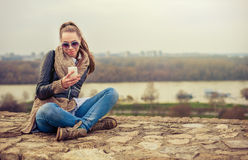 Young woman using mobile on the fortress Stock Image