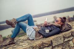 Young woman using mobile on the fortress Stock Images