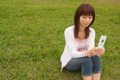 Young woman using mobile phone. Young woman sitting on grass and using mobile phone Stock Image