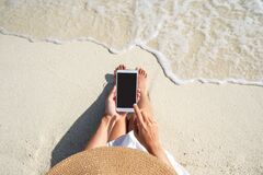 Free Young Woman Using Mobile Phone At Beautiful Tropical White Sand Beach With Wave Foam And Transparent Sea, Summer Vacation And Stock Image - 220648821