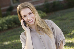 Young woman using mobile phone. A beautiful young woman using a mobile phone outdoors Stock Photos