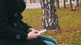 Young woman using a mobile phone on a bench in the city park. A Girl holds a Mobile Phone in hands and controls finger gestures and looks at social networks stock video footage