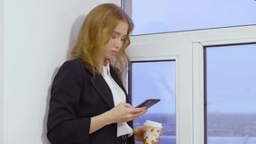 Young woman using mobile phone for browsing email and holding coffee cup in hand stock video
