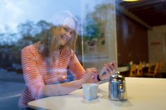 Young woman using a mobile phone in a cafeteria. View through the glass window of a young woman using a mobile phone in a cafeteria smiling as she reads a text Stock Images