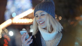 Young woman using mobile phone in a city at night. stock video