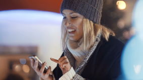 Young woman using mobile phone in a city at night. stock footage