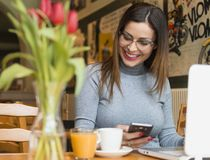 Young woman using mobile phone in Coffee shop stock photos