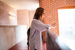 Young woman using mobile phone in corridor Stock Images