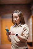 Young woman using mobile phone in corridor Royalty Free Stock Photo