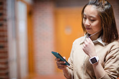 Young woman using mobile phone in corridor Royalty Free Stock Images