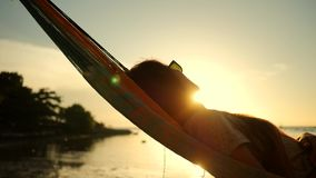 Young Woman Using Mobile Phone in Hammock at the Beach near the Sea with Beautiful Sunset on Background. Koh Phangan. Thailand. HD Slowmotion. 1080p stock footage