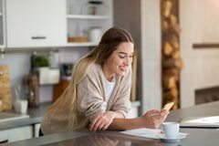 Young woman using mobile phone in the kitchen royalty free stock photography
