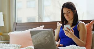 Young woman using mobile phone and laptop 4k. Young woman using mobile phone and laptop in bedroom 4k stock footage