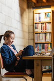 Young woman using mobile phone in library Stock Photography