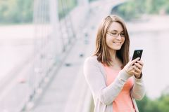 Young woman using mobile phone outdoors in a city. Beautiful young woman using mobile phone outdoors in a city Royalty Free Stock Photography