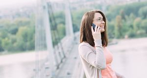 Young woman using mobile phone outdoors in a city. Beautiful young woman using mobile phone outdoors in a city Royalty Free Stock Image