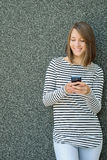 Young woman using mobile phone over gray background Royalty Free Stock Photo