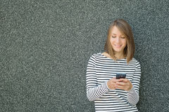 Young woman using mobile phone over gray background Royalty Free Stock Image