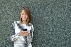 Young woman using mobile phone over gray background Stock Photo