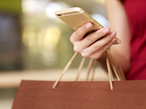 Young woman using mobile phone while shopping. Hand of a young woman carrying shopping bags using mobile phone Royalty Free Stock Images