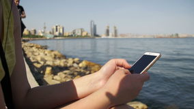 Young Woman using Mobile Phone Sitting on Embankment near the Sea and Skyscrapers of Megapolis stock video footage