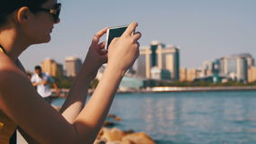 Young Woman using Mobile Phone Sitting on Embankment near the Sea and Skyscrapers of Megapolis stock video