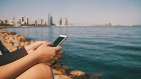 Young Woman using Mobile Phone Sitting on Embankment near the Sea and Skyscrapers of Megapolis stock footage