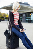 Young Woman Using Mobile Phone While Sitting On Luggage stock photos