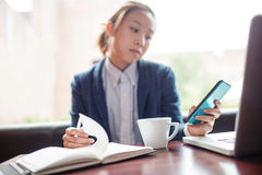Young woman using mobile phone while studying Royalty Free Stock Photography
